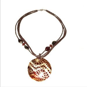 Brown beaded necklace with large charm.